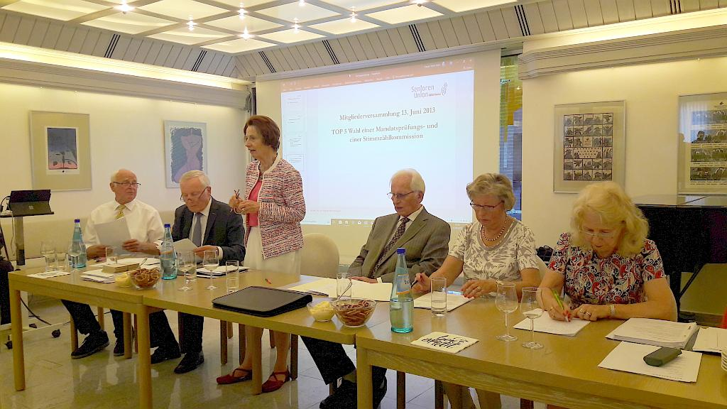 Helga Hammers als Sitzungsleiterin (stehend), (v.l.n.r.) Karl-Heinz Friedrich, Dr. Gerd Eckhardt, Gerhard Hübel, Ingrid Schappert, Dr. Gisela Schreiner